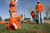 Skye Muzar, foreground, 8 months old, waits patiently as a tree is planted close to her including...