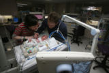 Kari and Joshua Whittington stare intently at their newborn Addison Nicole in the NICU of...