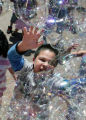 Danny Rico (cq) , 8 from Denver jumps for bubbles coming from a bubble tower outside of the...