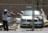 Dee Ann Chow, 16, looks at what's left of her Audi, two days after an explosion that destroyed a...