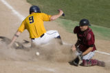 DLM8749  Regis' Sean Chase slides into home plate just before the throw reaches Mesa State catcher...