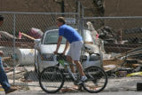 (at center) 12 year-old Andrew Hickey rides his bike at the site of an explosion that destroyed a...