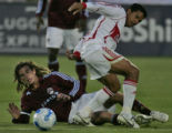 Colorado Rapids player Kyle Beckerman is knocked to the ground as he is tripped up by Chicago Fire...