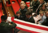 Family members watch as the US flag is replace on Stephen's casket during his funeral at Trinity...