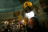 MJM978 Father Joseph Hirsch lights candles on the altar at the Holy Transfirguration of Christ...