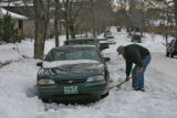 John Sells (cq) clears snow from around his car in the 900 block of Williams Street on Tuesday...