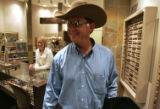 Art Gutterson tries on a pair of $160 sunglasses at Classic Creations Eyewear Tuesday afternoon...