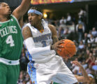 Denver Nuggets guard Allen Iverson looks to pass the ball being defended by Boston Celtics...