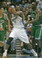 Denver Nuggets forward Nene pulls down a rebound surrounded by Boston Celtics defenders (left to...