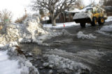 A front end loader moves snow from 16th Ave. and Jackson for Concrete Works of Colorado, the...