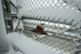 Wet snow clings to chain link fensing above I-25 as only a few vehicle continue on their way on...