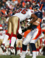 Tony Scheffler drops the ball as he his hit by Mark Roman in the first quarter of the Denver...