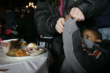 Dion-dri Amankwah, 4, gets help taking off his coat before diving into a turkey/ham dinner at the...