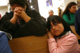 MJM067  Gloria Molina prays alongside her daughter, Andrea Molina, 7, during Christmas Mass at Our...