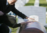 Rick Anderson (cq) comforts his wife Debra Anderson as they both reach down to touch the casket of...