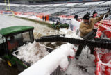 (DLM1223) - Daniel Ryszowski moves snow shoveled from the seats down a pipeline to a waiting all...