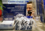 Continental Sales Agent Mark Freed (cq) left, waits on a customer at the Continental ticket...