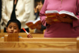 (DLM6847) -   A young boy peers over the pew as people at Our Lady of Peace Catholic Church in...