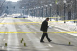 Denver police detective Mark Crider (Cq) crosses Speer Blvd, inspecting evidence at the scene...