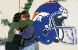 Broncos fans Colleen Schell (cq), left, hugs Debbie Ollila (cq), right, both of Wheatridge, after...