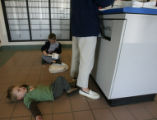 (DLM7540) -   Jack Cooper, 2, lies on the floor behind his mom, Danielle Cooper, as his brother...