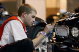 (DENVER, Colo., Mar. 29, 2005) Derek Moran (cq) of Professional Detailers, polishes the grill of...