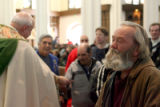 Tighe Chamberlane (cq), right, says a prayer after receiving a $20 gift from Monsignor Tom Fryar,...