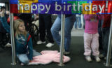 (DLM4352) -  Kayla Thorp, 8, of Casper, Wyo. sits below a sign wishing a happy birthday to...