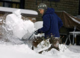 Casey Homuth (cq) shovels the front walkway at his Northwest Denver home as Rigby (cq), his one...