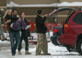 Eric Grengs carries Rachael Trotter across the snow and slush covered parking lot to the car after...