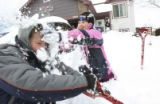 Cody Carlsen, 7, gets trashed in the face with a big pile of snow from his sister, Makayla, 10,...