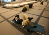 (DLM1272) -   James Allen, 24, of Dillon,Colo. sleeps in the baggage claim area at Denver...