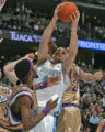 Denver Nugget Forward Linas Kleiza, middle, pulls down one of his 7 rebounds over Sacramento's...