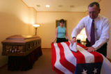 Rodney Ahlberg, right, of the Ahlberg Funeral Chapel and Crematory, irons the flag that covers the...