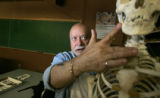 CU Professor Dennis Van Gerven points to a jaw bone on a skeleton. He and his group of diggers...