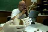 CU Professor Dennis Van Gerven looks at a jaw bone fragment. Asst. Paul Sandberg, PhD student in...