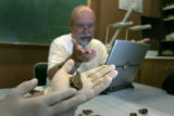 CU Professor Dennis Van Gerven points to a fragment of a jaw bone. He and his group of diggers...