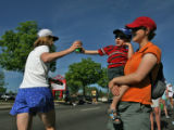 Julie Geller (cq) holds her son Ilan Geller Fine, 3 years old,  as they hand out water at Colfax...