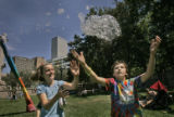 Morgan Cox (cq), 9, left, and Sage Thomas (cq), 8, right, chase after bubbles made from the Bubble...