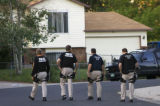 Members of the Immigration and Customs Enforcement's Fugitive Operations team walk down a suburban...