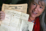 Kitty Brown (cq), of Ken Caryl, poses with old telegrams, photos and other memorabilia that once...