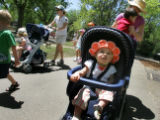 Elisa Son, 1, of Greenwood Village, waits as her mom, Susan Kaiser, (cq) picks up her brother...