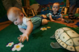 William Smith-Daigle, left, seven months old, and and his twin brother Henry, from Aurora, play in...