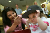 Berlyn Alfredsen (cq), 27 months, right, receives a Colorado Rockies cap signed by Todd Helton...