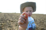 Soon to be a sixth generation farmer Ty Kissler, CQ, 4, holds a corn seed in his grandfather...