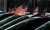 American flags fly on cars parked in a used car lot on West Colfax in Lakewood, CO, Sunday...