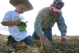 Everett Kissler, CQ, 55, right, checks water depth in a field of sugar beats with his grandson Ty...