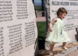 Two year-old Shea Dooley of Pittsburg, Pa. walks between the stones of a memorial that holds her's...