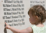 Two year-old Shea Dooley of Pittsburg, Pa. touches the name of her father on the Mountain Post...