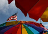 Two American flags are seen through colorful umbrellas at Heritage Square in Golden, CO, Sunday...